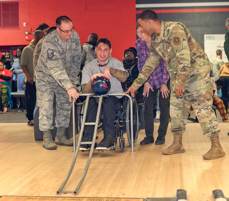 Master Sgt. Bryan Hess, 89th Maintenance Group, and Master Sgt. Jean Jean-Felix, 89th Communications Squadron, help Joshua Chartienitz, a participant in the tournament, bowl during the Special Olympics DC Adult Bowling Tournament in Hyattsville, Md., March 4, 2020. Over 30 Airman from Joint base Andrews volunteered at the event. (U.S. Air Force photo/Senior Airman Jalene A. Brooks)