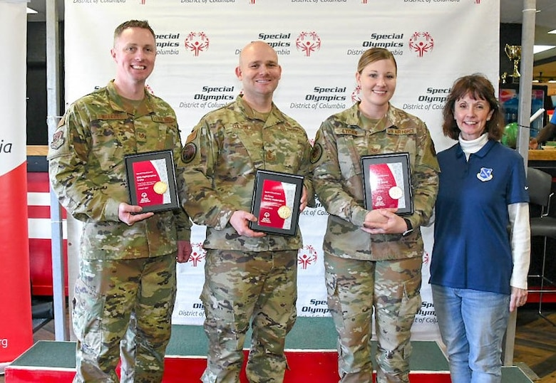Tech. Sgt. Martin Walcott, 89th Maintenance group; Chief Master Sgt. Matthew Coltrin, Air Force District of Washington; Staff Sgt. Rachel Lycan, Air Force Review Board; and Johanna O'Neill, Air Force District of Washington commander's secretary, pose for a photo after accepting the Special Friend Award on behalf of their units for volunteering at the Special Olympics DC's Adult Bowling Tournament in Hyattsville, Md., March 4, 2020. The Special Friend Award was awarded to each command that provided more than 10 volunteers on the day of the tournament. (U.S. Air Force photo/Senior Airman Jalene A. Brooks)