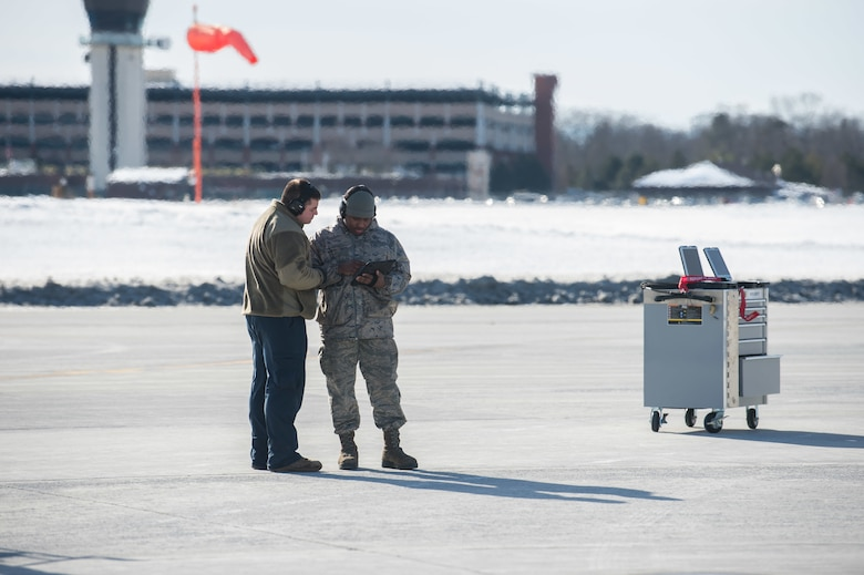 Crew chiefs assigned to the 158th Maintenance Group, 158th Fighter Wing, Vermont Air National Guard, work on a mobile device on the flight line.