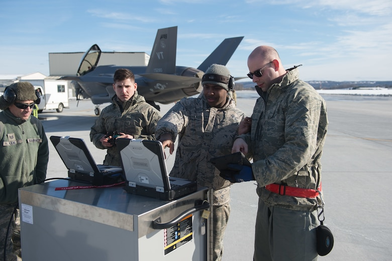 Crew chiefs assigned to the 158th Maintenance Group, 158th Fighter Wing, Vermont Air National Guard, work on a mobile device and computers on the flight line