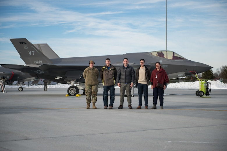 Tech. Sgt. Leah Curtin, a crew chief assigned to the 158th Maintenance Group, 158th Fighter Wing, Vermont Air National Guard, gathers together with Kessel Run employees in front of an F-35 Lightning II