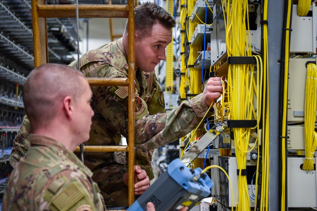 One service member and two men troubleshoot wiring.
