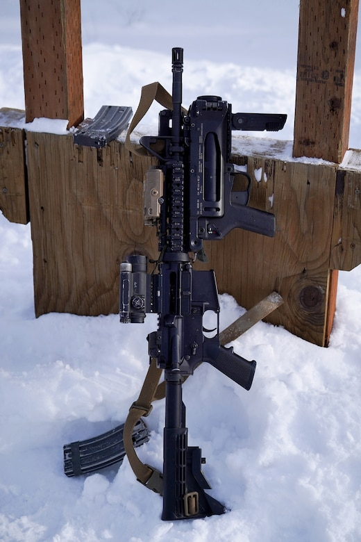 An M-4 carbine with attached M-320 40mm grenade launcher rests on a shooting platform.