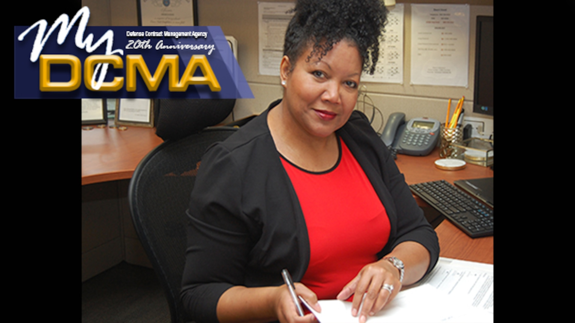 A woman, who is wearing a black blazer, reviews work materials, while sitting at her desk.
