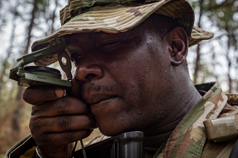 Photo of an Airman shooting an azimuth during land navigation training.
