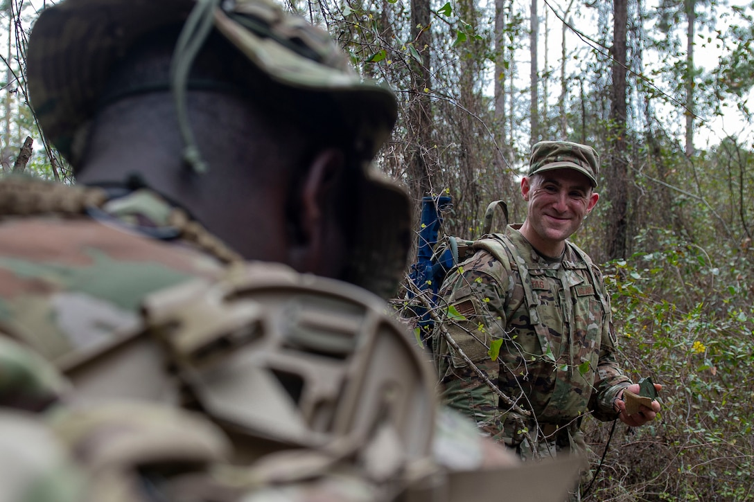 Photo of Airman sharing a laugh during land navigation training.