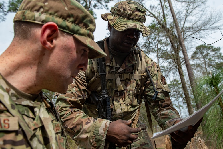 Photo of Airmen discussing strategy during land navigation training.