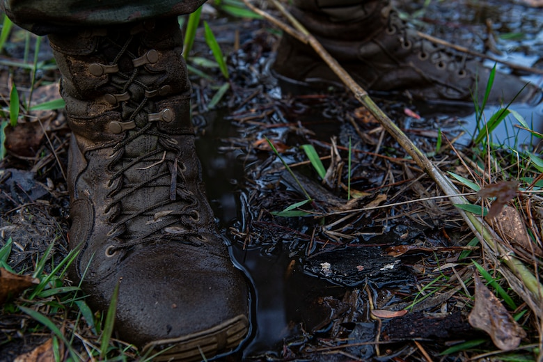 Photo of an Airman stands in mud during land navigation training.