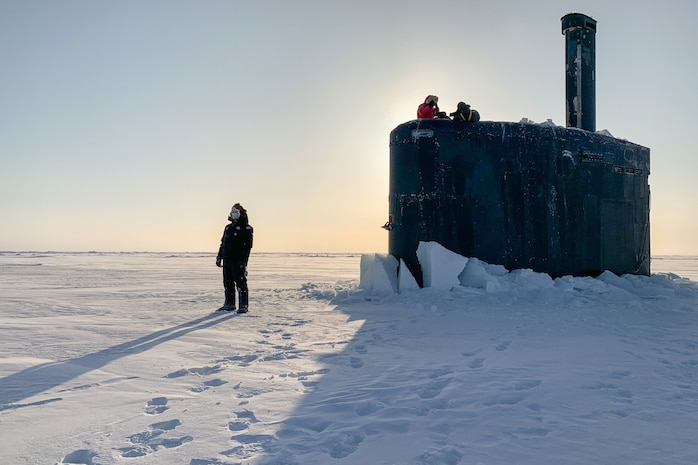 A service member stands on ice as other service members watch from a submarine.