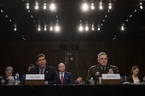 Two men sit behind a desk and testify.