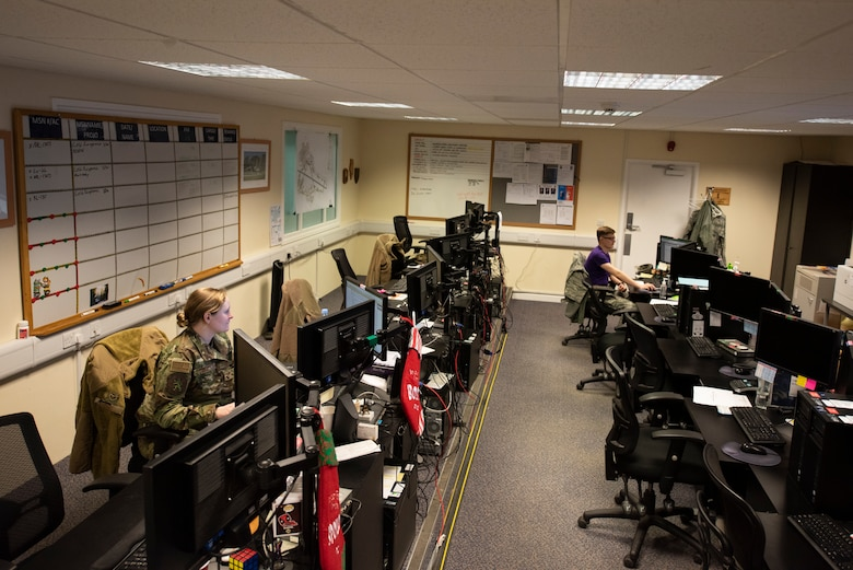 Staff Sgt. Nicole Nagy, 100th Logistics Readiness Squadron wing air expeditionary force reporting tool manager, and Airman 1st Class Ethan Morrow, 100th LRS logistics apprentice, work inside the installation deployment readiness cell March 6, 2020, at RAF Mildenhall, England. The IDRC oversees the deployment process for all units on base, as well as certain geographically separated units. (U.S. Air Force photo by Airman 1st Class Joseph Barron)