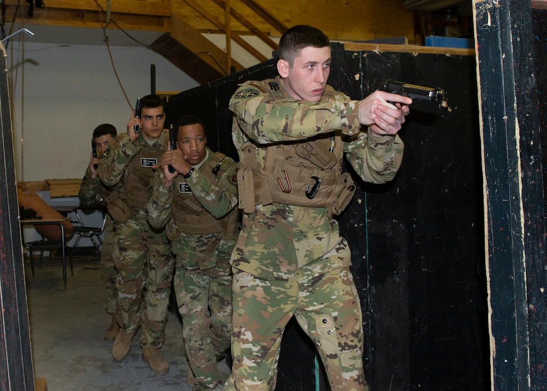 photograph of four Airmen with weapons in their hands as they move along a wall inside training area
