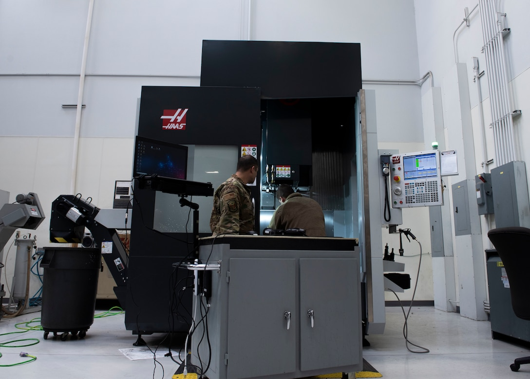 U.S. Air Force Tech. Sgt. Kevin Collins, 366th Maintenance Squadron aircraft metals technology section chief and U.S. Air Force Airman 1st Class Luke Haener, 366th MXS aircraft metals technology craftsman stand in front of a metal cutting or CNC machine, March 2, 2019, at Mountain Home Air Force Base, Idaho. The HandyScan sends the 3D image to the computer that then sends it to the CNC machine. (U.S. Air Force photo by Airman Natalie Rubenak)