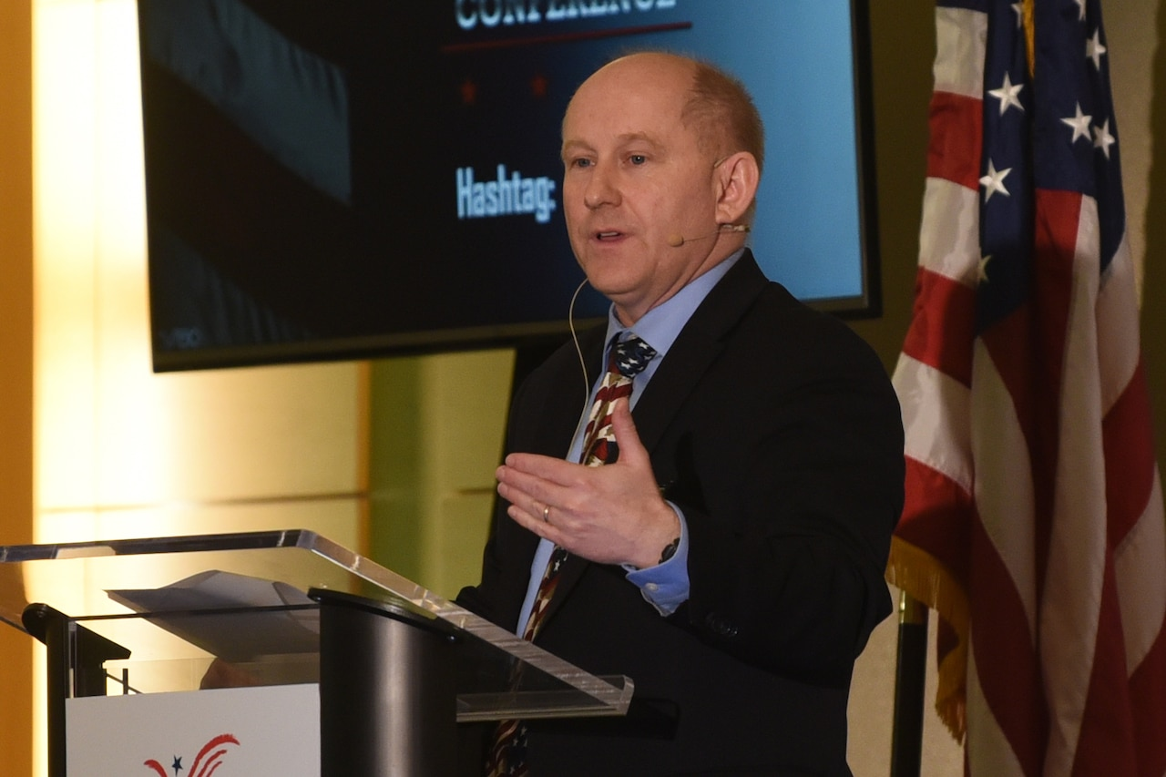 Man speaks from behind a lectern; the U.S. flag is behind him.