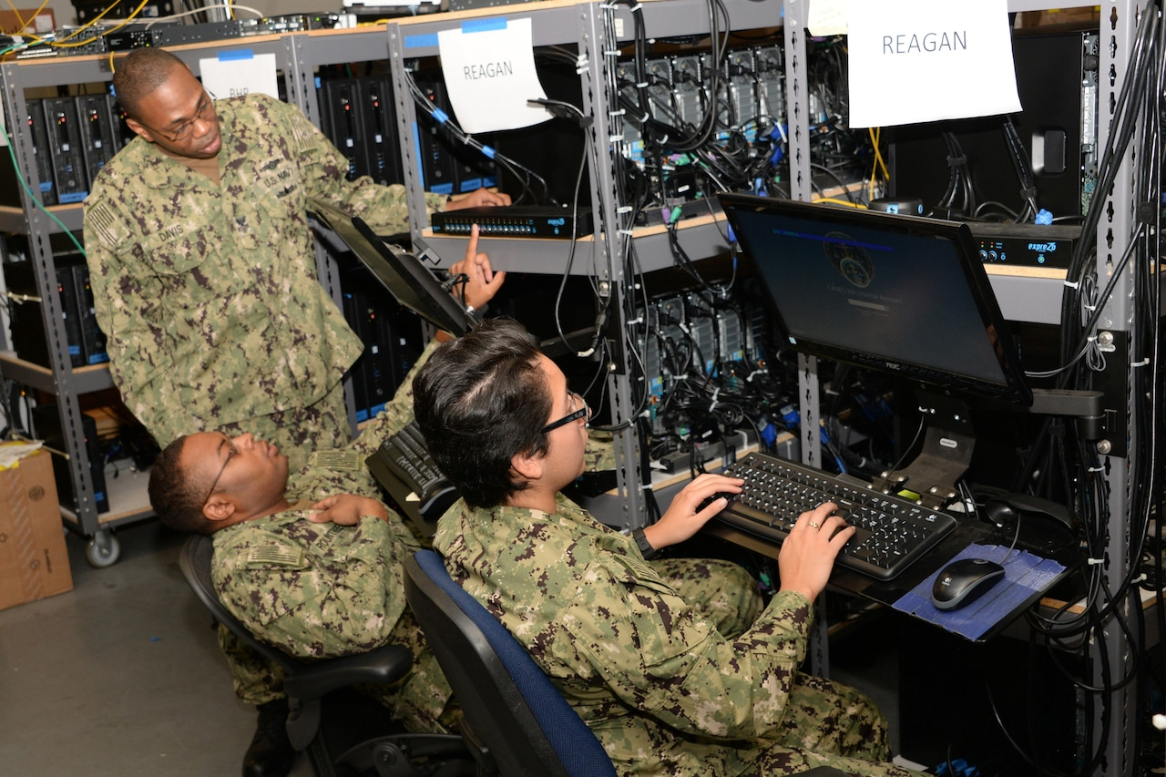 Three service members work on computer equipment.
