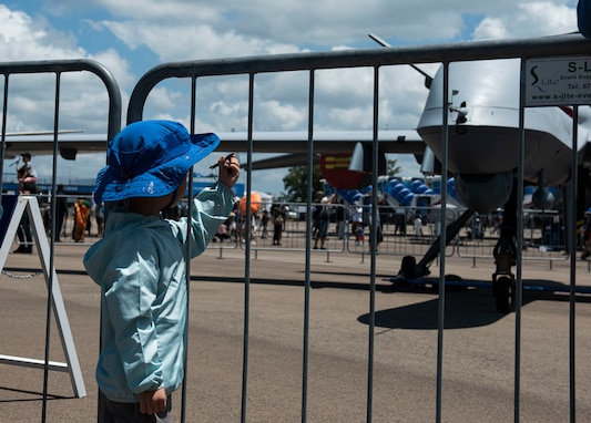 A child marvels at his toy plane while he stands in front of the MQ-9 Reaper at Singapore Airshow.