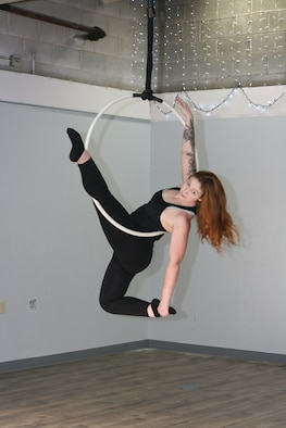 "Staff Sgt. Rachel Loftis, a public affairs specialist with the 193rd Special Operations Wing, Middletown, Pa., completes a lyra workout, also known as aerial hoop - the art of performing acrobatics using a hoop connected to the ceiling. Loftis first pursued aerial acrobatics while stationed at Nellis Air Force Base, Las Vegas, which she attributes to the robust local ""circus community"" there and the desire to find a fitness program that was effective and held her interest. (U.S. Air National Guard photo by Tech. Sgt. Claire Forbes)"