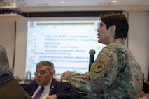 White female in green camouflage stands holding a microphone, a white man in a suit sits in the audience with a large screen and slide up in the background.