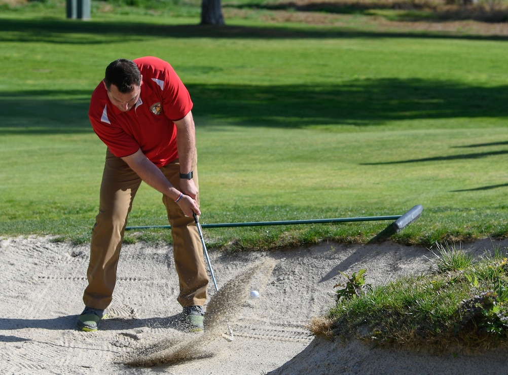 A U.S. Marine Corps Staff Sgt. Jonathan Wheeler practices chipping out of the sand before moving to the next hole during the 2020 Marine Corps Trials at Marine Corps Base Camp Pendleton, Calif., March 4. The Marine Corps Trials promotes recovery and rehabilitation through adaptive sports participation and develops camaraderie among recovering service members and veterans