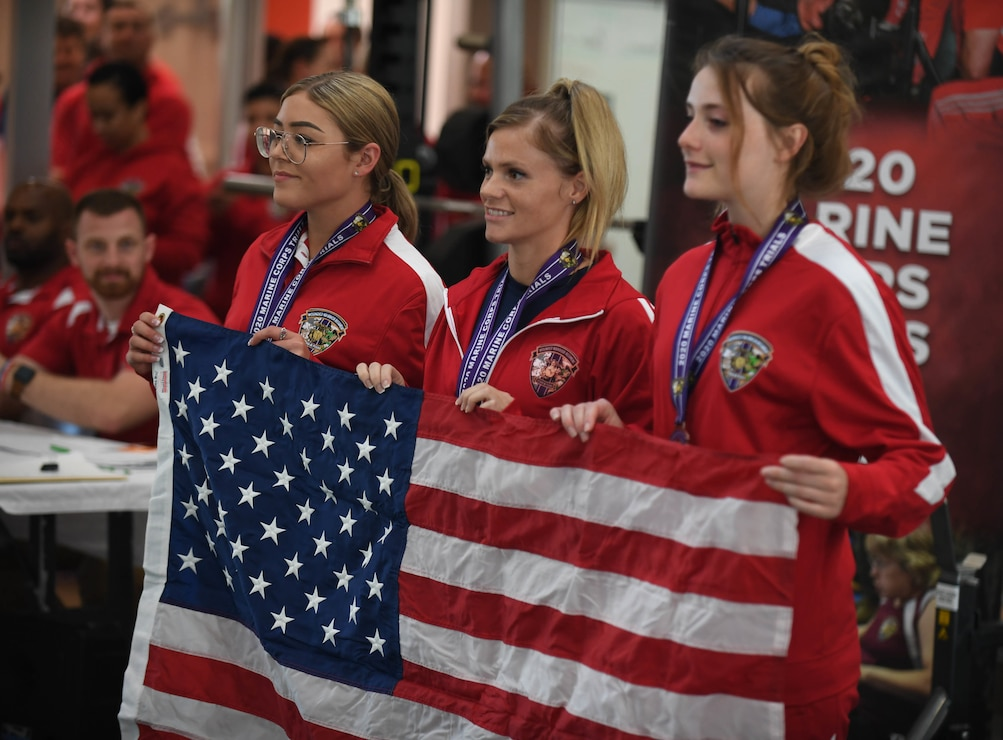U.S. Marine Corps athletes Clair Morrow (left), Sasha Savage (middle), and Kathryn Fisher (right) hold up the American flag after medalling at the 2020 Marine Corps Trials powerlifting competition at Marine Corps Base Camp Pendleton, Calif., March 4. The Marine Corps Trials is an adaptive sports event involving more than 200 wounded, ill or injured Marines, Sailors, veterans and international competitors.
