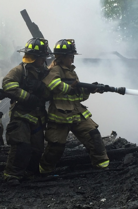 Airman 1st Class Sinéad Brosnan, 27th Special Operations Health Care Operations Squadron aerospace medical technician, uses a fire hose to put out the embers of a fire in Florida, New York, in 2016. Originally Brosnan was a volunteer EMT but began volunteering as a firefighter when New York state passed a law requiring certification to be an EMT. (Courtesy Photo)