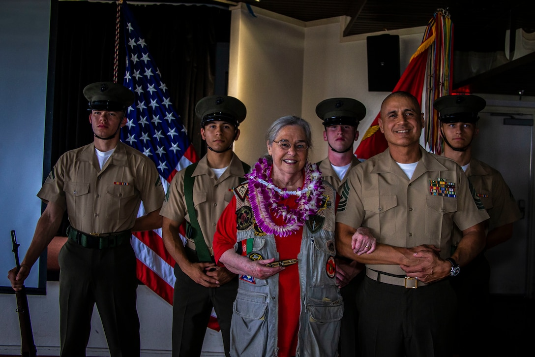 Mrs. Barbara Mathews, U.S. Marine Corps 1st Sgt. Erick Velez, Weapons Company first sergeant, 1st Battalion, 3rd Marine Regiment, and the 3rd Marine Regiment color guard pose for a group photo during an Honorary Marine ceremony, Marine Corps Base Hawaii, March 6, 2020. The Honorary Marine title is designed to reinforce the special bond between the American people and the Marine Corps by recognizing individuals in the civilian community who have made extraordinary contributions to the Marine Corps. Mrs. Mathews earns this prestigious honor for volunteering over 10 years of her personal time, talents and money capturing photo and video of hundreds of Marine Corps ceremonies, including memorials and special events surrounding the wars in Iraq and Afghanistan. (U.S. Marine Corps photo by Cpl. Matthew Kirk)