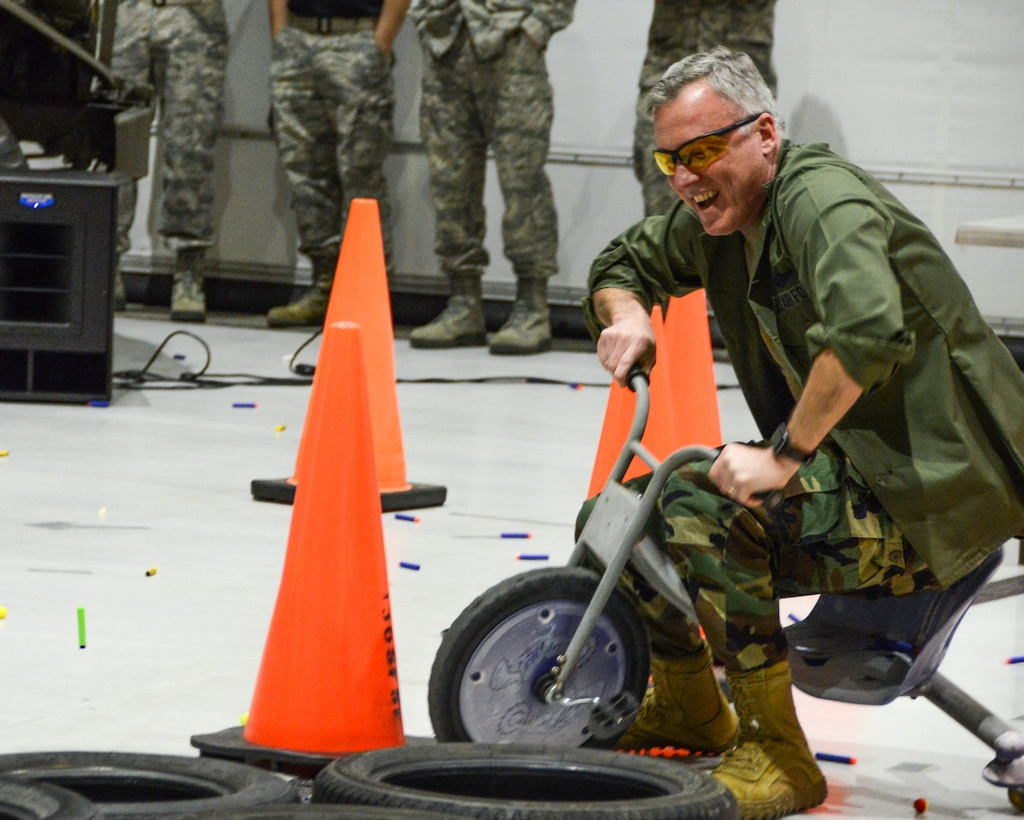 A Texas Air National Guard Colonel dismounts a tricycle on an obstacle course.
