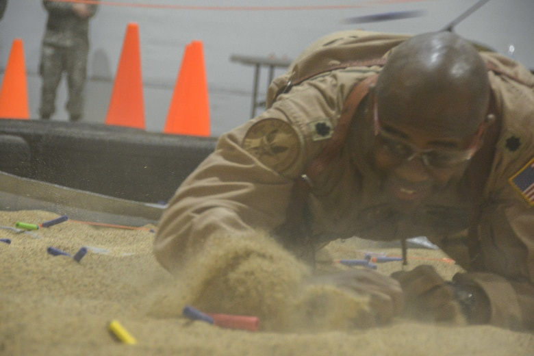 A Texas Air National Guard Lieutenant Colonel low-crawls through sand while being pelted with foam darts.
