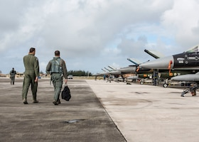 Lt. Col. Julio Rodriguez (right), an 18th Agressor Squadron pilot, and his brother Lt. Col. Antonio Rodriguez (left), a 506th Expeditionary Air Refueling Squadron pilot, walk to an F-16C Fighting Falcon February 27, 2020 at Andersen Air Force Base, Guam.