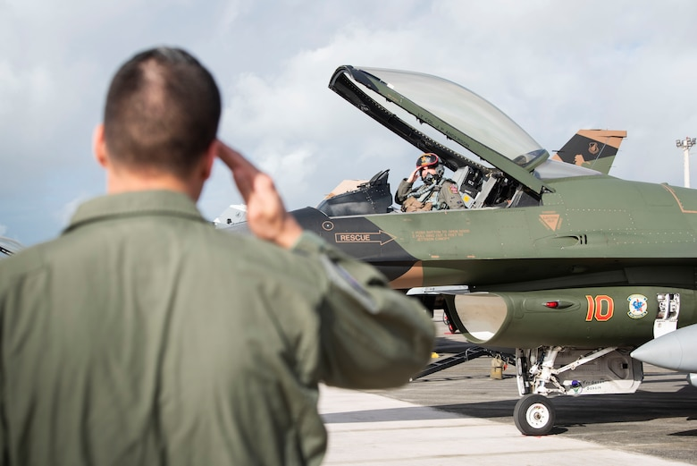 Lt. Col. Julio Rodriguez salutes his brother Lt. Col. Antonio Rodriguez before takeoff in an F-16C Fighting Falcon February 27, 2020 at Andersen Air Force Base, Guam.