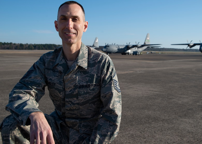 Master Sgt. Matthew Sheley poses on the flight line with C-130J aircraft in the background.