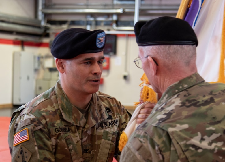 Col. Carlos E. Gorbea, left, incoming commander of the 361st Civil Affairs Brigade, passes the unit colors to Command Sgt. Maj. Michael S. McGregor, during a change of command ceremony held on Kleber Kaserne in Kaiserslautern, Germany, March 7, 2020.