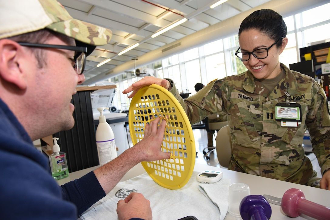 U.S. Army Capt. Jacqueline Tamayo, right, Landstuhl Regional Medical Center occupational therapy assistant chief, coaches Petty Officer 2nd Class Even Parker, Armed Forces Network Europe photographer, through hand strength exercises at LRMC, Germany, March 3, 2020. A patient would go to the occupational therapists at LRMC for issues including PTSD resulting from combat or sexual trauma, traumatic brain injury, wrist fracture, tendon laceration, a broken finger, and memory or movement problems resulting from a stroke.