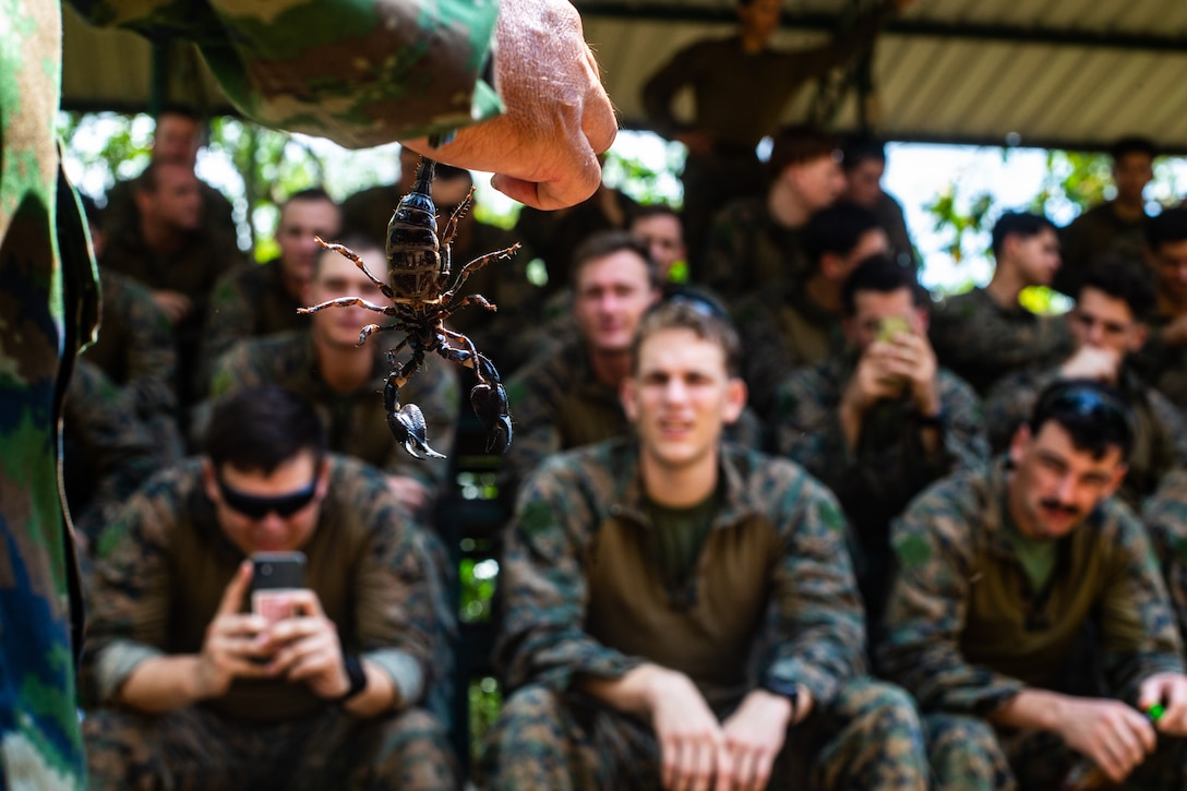 A Royal Thai Marine showcases a scorpion to U.S. Marines during jungle survival training at Camp Lotawin, Kingdom of Thailand, March 4.