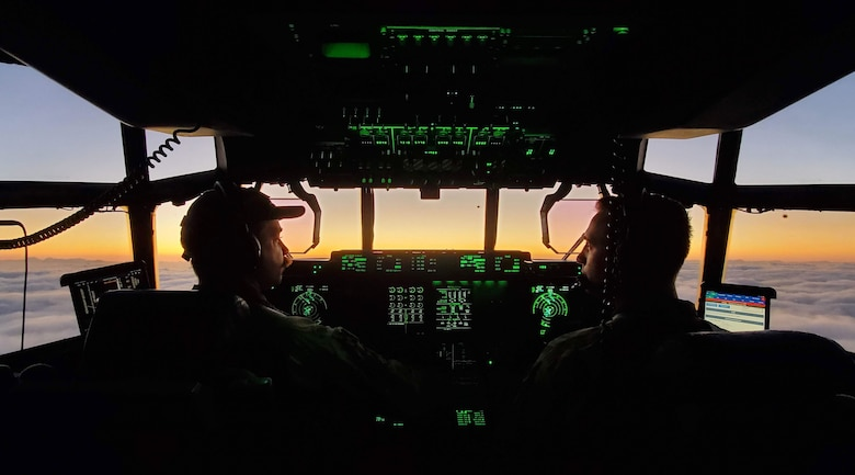 Two Airmen fly a plane above the clouds with a sunset in the background.