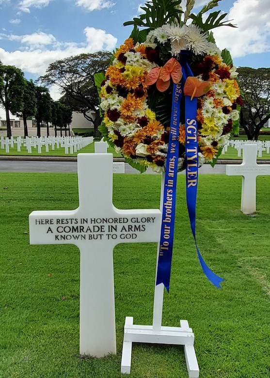 A wreath sits next to an unmarked headstone.