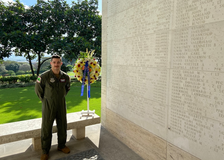 An Airman stands next to a wall with names on it.