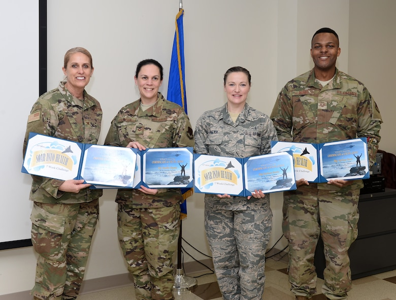 A picture of a woman awarding three people with certificates.