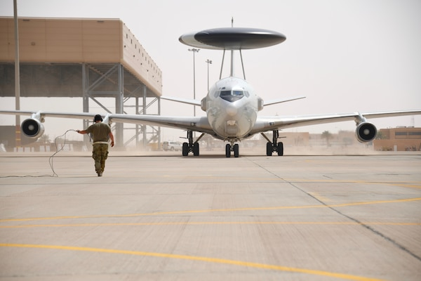 U.S. Air Force Senior Airman Shane Ice, 380th Expeditionary Maintenance Squadron crew chief taxies an E-3 Sentry, on the flight line at Prince Sultan Air Base, Kingdom of Saudi Arabia on March 1, 2020. The E-3s forward deployed to PSAB from Al Dhafra Air Base, United Arab Emirates, as part of an agile combat employment mission meant to test the squadron's ability to conduct missions in the region from an austere location. (U.S. Air Force photo by Tech Sgt. Michael Charles)