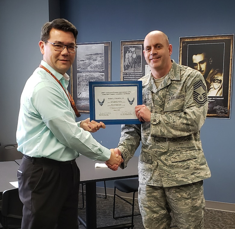 Mr. Michael Steele, National Air and Space Intel Center process manager, presents the USAF Continuous Process Improvement Green Belt Program Completion Certificate to Chief Master Sgt. Albert Franklin, 14th Intelligence Squadron, earlier this year. Green Belt is part of the Air Force Continuous Improvement Process, which increases operational capabilities while reducing associated costs by applying proven techniques to all processes associated with fulfilling the Air Force mission.