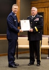 Brig. Gen. Richard Neely of Springfield, Illinois, the Adjutant General of the Illinois National Guard, presents Brig. Gen. Michael Glisson of Festus, Missouri, with his certificate of discharge from the United States Army at a retirement ceremony March 7, at the Illinois Military Academy in Springfield, Illinois.