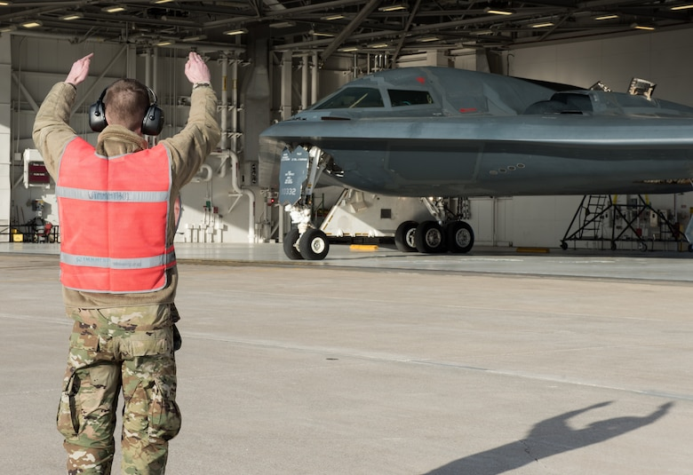 A crew chief assigned to the 131st Bomb Wing marshals a B-2 Spirit onto the flightline at Whiteman Air Force Base, Missouri, March 8, 2020. The B-2 is slated to support U.S. Strategic Command Bomber Task Force operations in Europe. These missions provide opportunities to train and work with our allies and partners in joint and coalition operations and exercises. (U.S. Air Force photo by Airman 1st Class Christina Carter)
