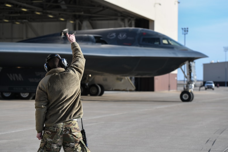 """U.S. Air National Guard Tech. Sgt. Justin Aeckerle, a B-2 crew chief assigned to the 131st Maintenance Squadron, signals a final good luck hand signal to a B-2 Spirit pilot before takeoff at Whiteman Air Force Base, Missouri, March 8, 2020. The B-2 """"Spirit of Washington"""" launched from Whiteman AFB to support U.S. Strategic Command Bomber Task Force operations in Europe. The 131s Bomb Wing's 131st MXS is the total-force partner unit to the 509th Bomb Wing. (U.S. Air Force photo by Tech. Sgt. Alexander W. Riedel)"""