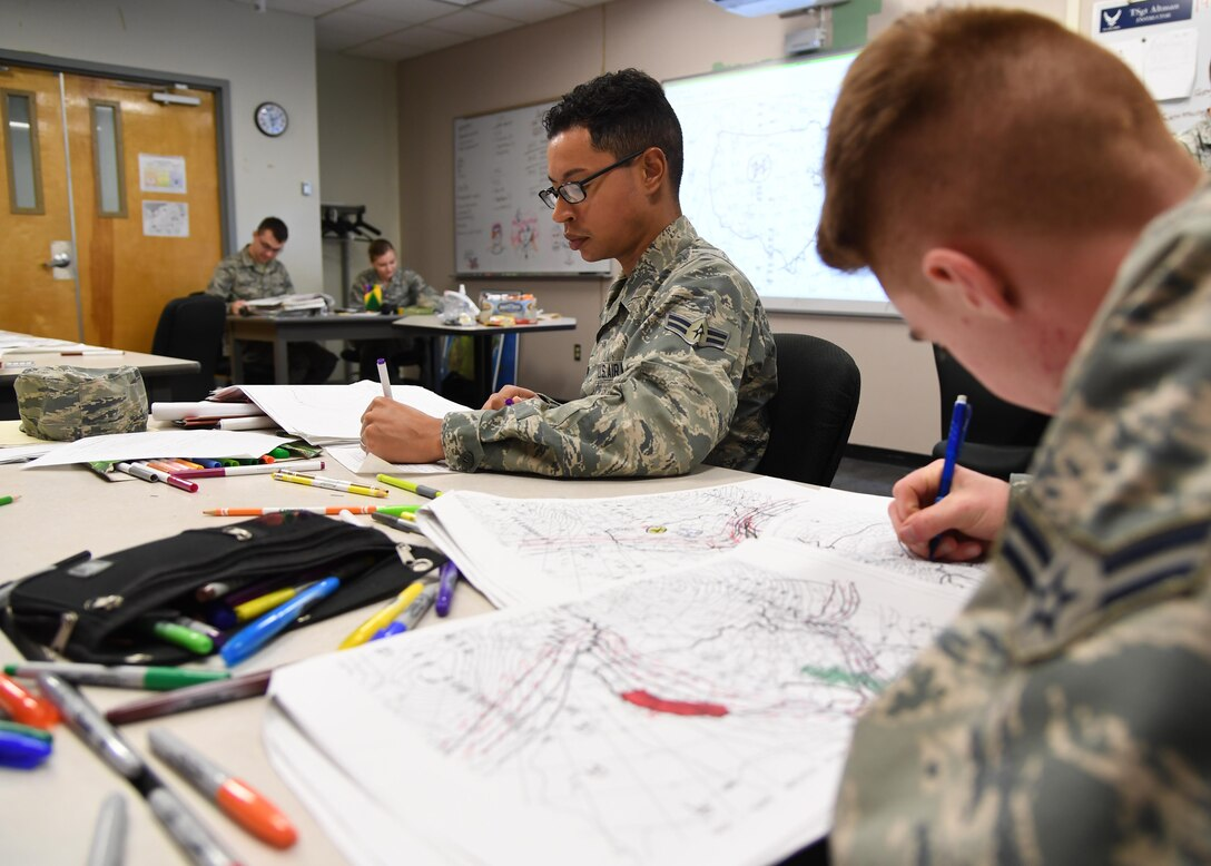 U.S. Air Force Airmen 1st Class John Sanabria and Grayson Egbert, 335th Training Squadron students, plot data on weather charts used for training inside of the the Joint Weather Training Facility at Keesler Air Force Base, Mississippi, Jan. 27, 2020. The weather apprentice course, which graduated 650 students this past year, takes 151 academic days to complete. Approximately 7,400 students go through the 335th TRS's 13 Air Force Specialty Codes each year. (U.S. Air Force photo by Kemberly Groue)