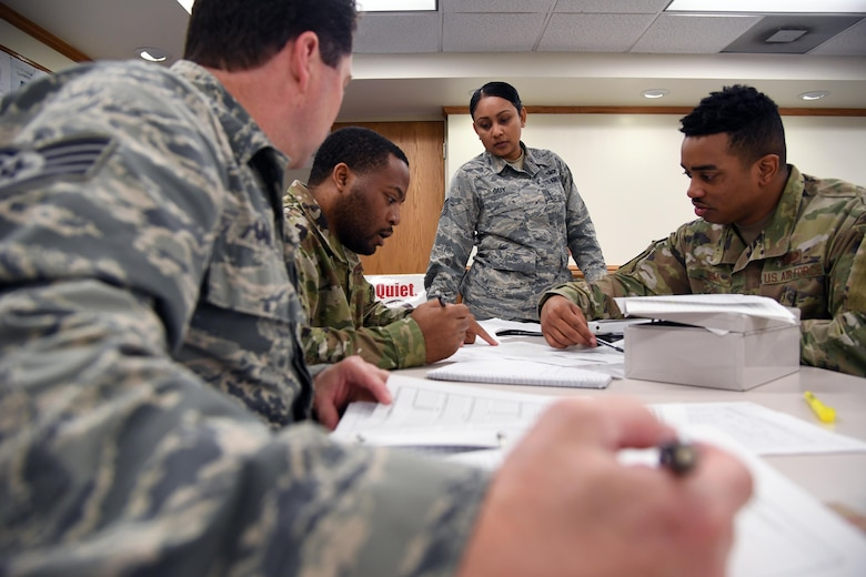 U.S. Air Force Tech. Sgt. Leona Guy, 335th Training Squadron instructor, observes as Staff Sgts. Brian Lavriha, Demetrius Sharpe and Aaron Bush, 335th TRS students, complete class work for the finance management course inside Allee Hall at Keesler Air Force Base, Mississippi, Feb. 3, 2020. This course, which graduated 220 students this past year, takes nine academic days to complete. Approximately 7,400 students go through the 335th TRSs 13 Air Force Specialty Codes each year. (U.S. Air Force photo by Kemberly Groue)