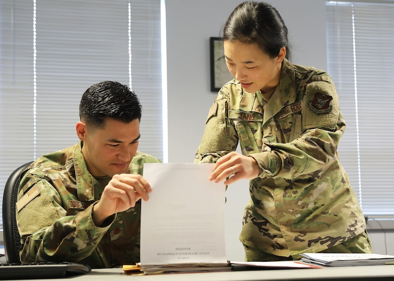 Lt. Col. Hanna Yang, 446th Airlift Wing staff judge advocate, reviews a legal file with Maj. Drew Nishiyama, 446th AW judge advocate, March 7, 2020.