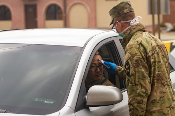 Soldier measures temperature of a driver entering post.