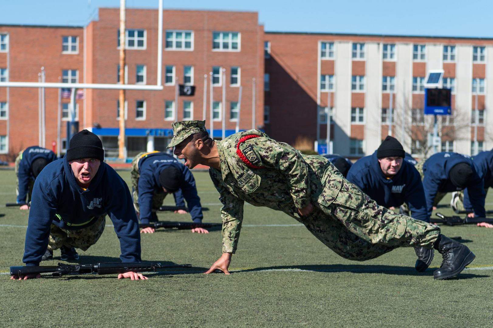 Recruit division commander assigned to Officer Training Command Newport, in Newport, Rhode Island, corrects Officer Candidate School student's form during remedial physical training, March 9, 2020 (U.S. Navy/Darwin Lam)