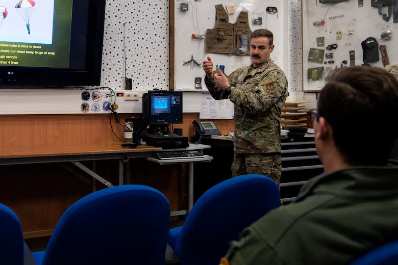 U.S. Air Force Master Sgt. Adam Murphy, 52nd Operations Support Squadron Survival, Evasion, Resistance, and Escape operations section chief, center, teaches Capt. Daniel Hayduchok, 480th Fighter Squadron pilot, right, how to troubleshoot potential parachute issues at Spangdahlem Air Base, Germany, March 6, 2020. Pilots routinely participate in SERE training to proactively be ready for any potential emergency scenario. (U.S. Air Force photo by Senior Airman Valerie R. Seelye)