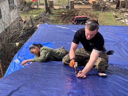 U.S. Marine Corps Sgt. Lakezia Ortiz, left, a recruiter from RSS Hendersonville and Capt. Kyle Cawthon, executive officer at RS Nashville, secure tarps on top of the roof of a damaged home in North Nashville, March 5, 2020. The Marines worked with local authorities and volunteers to assist with the clean-up and recovery efforts in the local area after severe storms and tornados blew across Middle Tennessee on March 3rd, 2020, which caused death, injury and widespread property damage. (U.S. Marine Corps photo by Sgt. Devin Phommachanh)